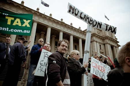 outside victoria's parliament house are protestors and banners opposed to the carbon price